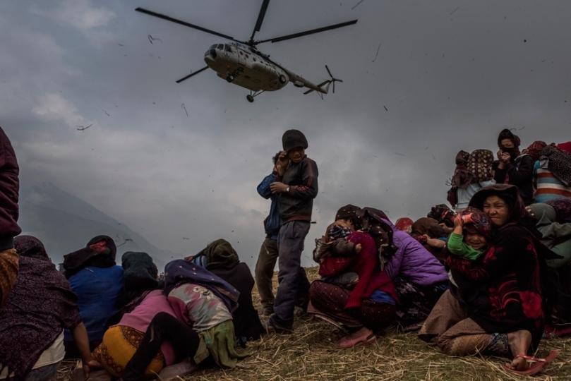 Nouvelles générales, 3e prix - Histoires Daniel Berehulak, Australie, pour The New York Times Suites d'un séisme 9 mai 2015, Népal. Des villageois népalais observent un hélicoptère cueillir une équipe médicale venue à leur secours depuis une zone d'atterrissage de fortune aménagée dans le village de Gumda.
