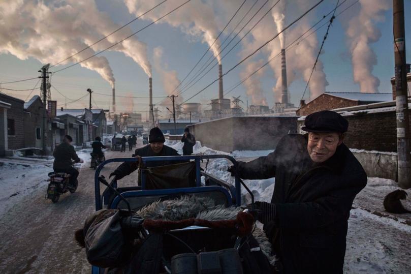 Vie quotidienne, 1er prix – Photos uniques Kevin Frayer, Canada, pour Getty Images Dépendance de la Chine au charbon 26 novembre 2015. Des citoyens chinois traînent un triporteur dans un quartier à proximité d'une centrale électrique au charbon, dans le Shanxi, en Chine. Un historique de forte dépendance à la combustion du charbon comme source d'énergie fait de la Chine l'émetteur de près du tiers du dioxyde de carbone (CO2) émis dans sur la planète. Ce polluant toxique est largement cité par les scientifiques et les environnementalistes comme principale cause du réchauffement climatique.