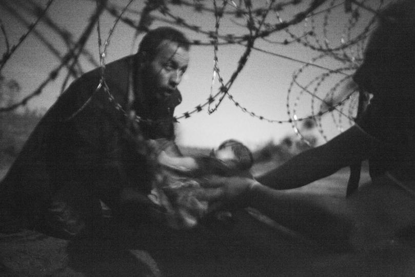 Prix Photo de l'année 2015 – World Press Photo Warren Richardson, Australie Espoir d'une nouvelle vie, 28 août, Frontière serbo-hongroise. 28 août 2015. Un bébé est remis à travers des fils barbelés à un réfugié syrien parvenu à traverser la frontière séparant la Serbie de la Hongrie, près de Röszke. La Hongrie durcissait sa position à l'égard des réfugiés tentant d'entrer dans leur pays. Dès juillet, ce pays avait amorcé l'implantation d'une clôture de quatre mètres longeant sa frontière avec la Serbie, scellant ainsi le pays, à l'exception de ses routes officielles. Les réfugiés ont tenté plusieurs moyens de passer avant la finalisation de la clôture, le 14 septembre. Durant cette nuit-là, le groupe avait passé quatre heures, dissimulé dans un verger, tentant d'éviter les barrages policiers et le poivre de Cayenne, tout en essayant de se frayer un chemin.